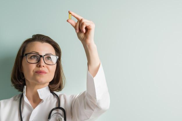 Femme médecin avec capsule de vitamine.