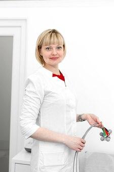 Femme médecin cardiologue avec électrodes de cardiographe dans ses mains