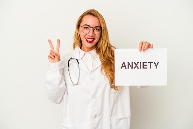 Femme médecin caucasien tenant une pancarte d'anxiété isolée sur fond blanc montrant le numéro deux avec les doigts.