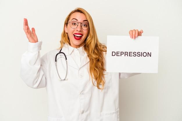 Femme médecin caucasien tenant une pancarte de dépression isolée sur fond blanc recevant une agréable surprise, excitée et levant les mains.