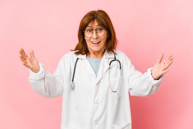 Femme médecin caucasienne d'âge moyen isolée recevant une agréable surprise, excitée et levant les mains.