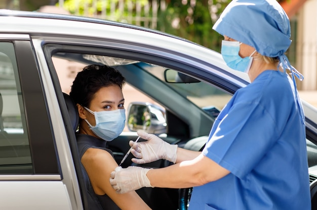 Une femme médecin caucasienne de la santé publique en uniforme d'hôpital bleu et un support de masque facial tiennent l'injection d'aiguille de seringue de vaccin sur l'épaule d'une patiente dans la file d'attente de vaccination de voiture.