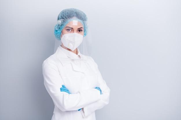 Une femme médecin confiante porte un masque médical protecteur isolé sur un mur gris