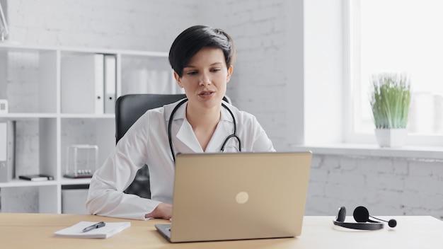 Femme médecin consultant à distance du patient en ligne à l'aide d'une caméra web sur un ordinateur portable