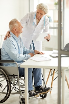 Femme médecin consultant un homme âgé