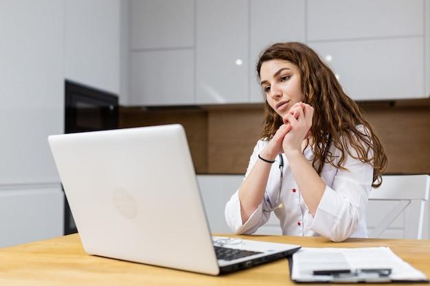 Une femme médecin consulte en ligne à l'aide d'un ordinateur portable portant des vêtements médicaux