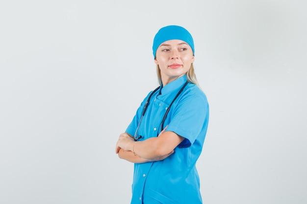 Femme médecin croisant les bras tout en regardant en arrière en uniforme bleu et à la recherche d'espoir.