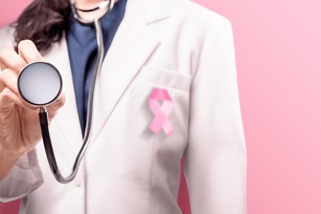 Une femme médecin dans une blouse blanche à l'aide d'un ruban rose à l'aide d'un stéthoscope sur fond rose