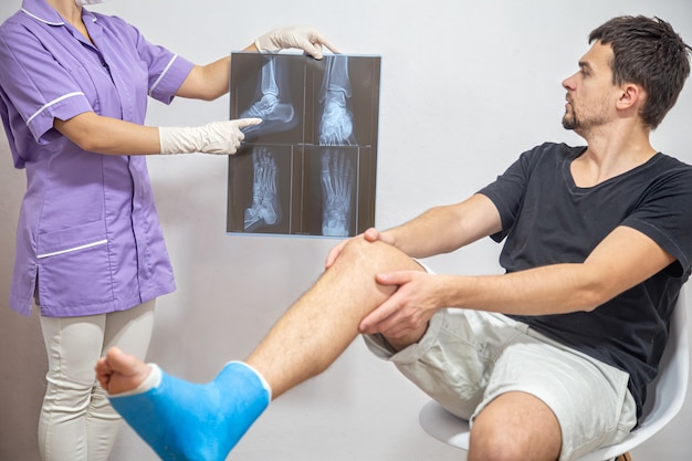 Une femme médecin dans une blouse médicale bleue explique à un patient de sexe masculin avec une jambe cassée le résultat d'une radiographie.