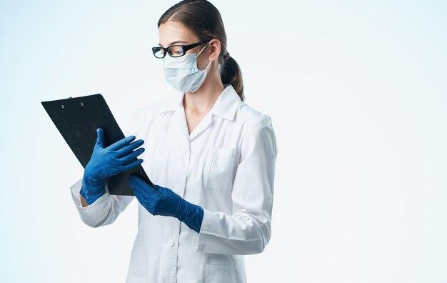 Femme médecin dans une blouse médicale et des tests de vaccination avec des gants bleus.