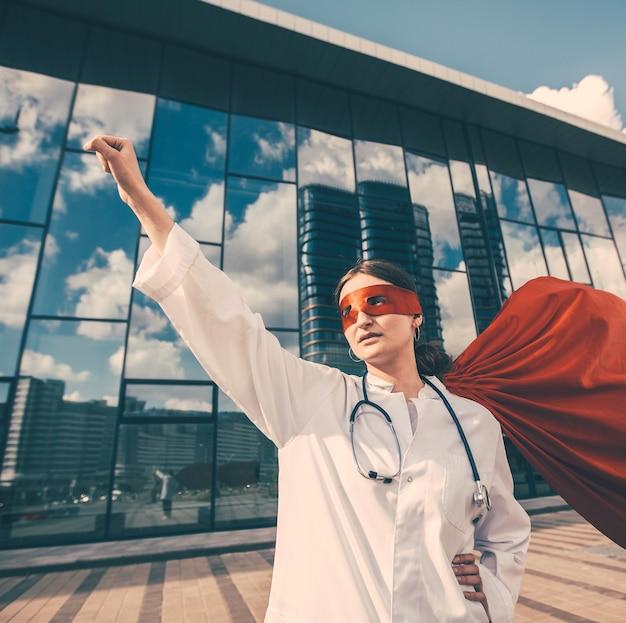 Une femme médecin dans une cape de super-héros est prête à vous aider. photo avec un espace de copie.