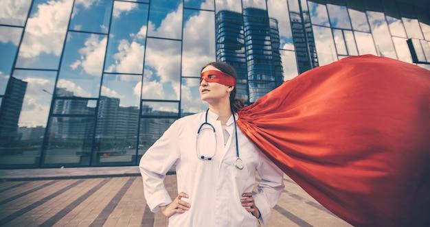 Une femme médecin dans un imperméable de super-héros regarde une rue de la ville. photo avec un espace de copie.