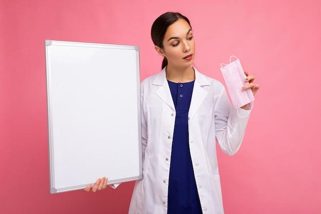 Femme médecin dans un manteau médical blanc tenant un tableau blanc avec espace de copie pour le texte et la protection