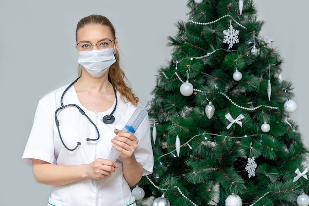 Une femme médecin dans un masque médical de protection tient une grande seringue