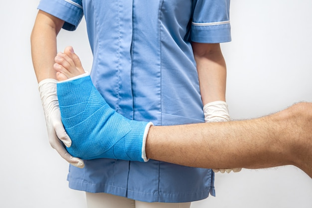 Femme médecin dans une robe médicale bleue vérifiant la jambe cassée sur un patient de sexe masculin.