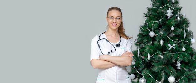 Femme médecin dans un uniforme blanc sourit à côté d'un arbre de noël. félicitations au médical