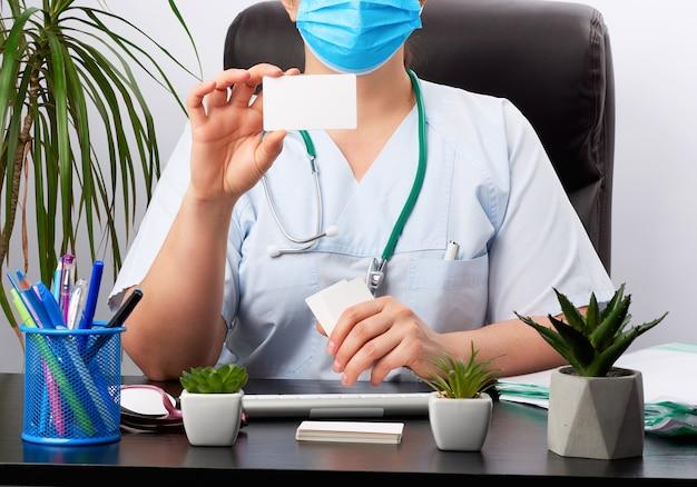 Femme médecin dans un uniforme médical est assis à une table dans une chaise en cuir marron et détient une carte de visite vierge blanche rectangulaire