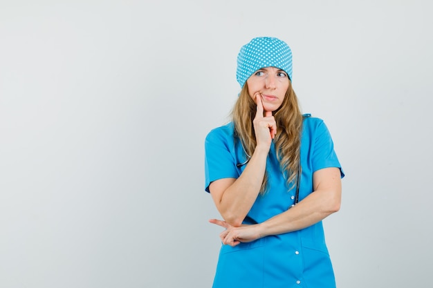 Femme médecin debout dans la pensée pose en uniforme bleu et à la recherche d'hésitant.