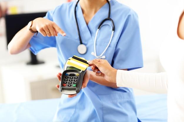 Femme médecin debout dans son bureau avec terminal de paiement