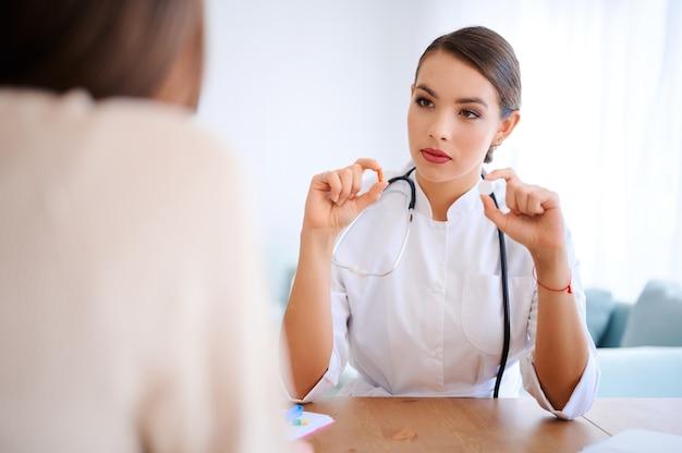 Femme médecin détient différentes pilules et discuter avec le patient à l'intérieur