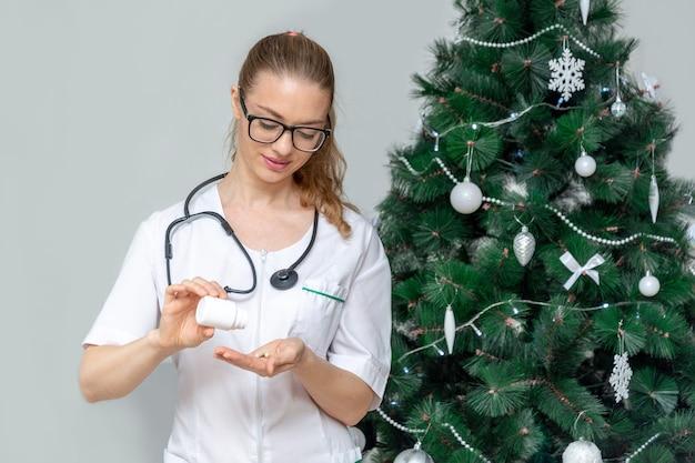 Femme médecin détient des pilules en arrière-plan d'un arbre de noël. traitement de la digestion de
