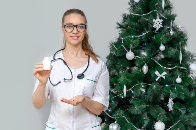 Une femme médecin détient des pilules dans l'espace d'un arbre de noël