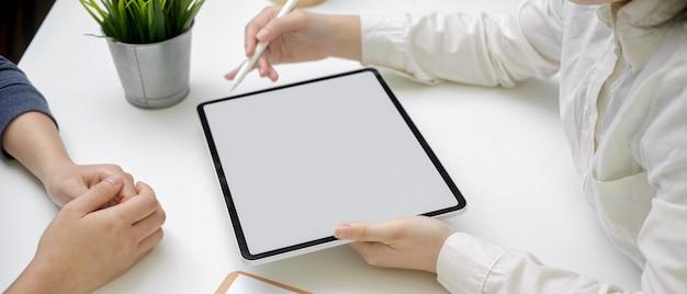 Femme médecin diagnostiquant une patiente tout en regardant le dossier médical sur une tablette écran vide