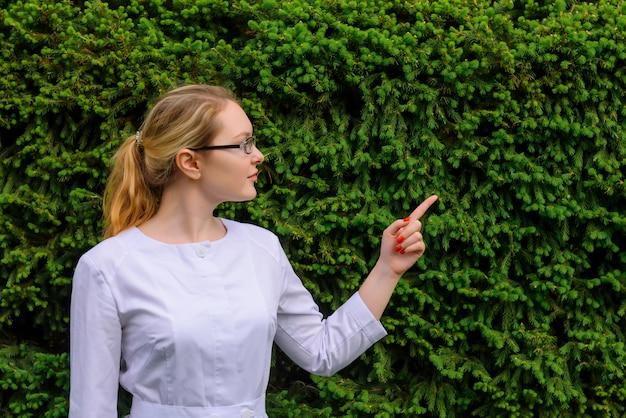 Femme médecin avec doigt pointe vers le haut. nutritionniste en blouse blanche et verres sur feuillage vert avec copie espace. image pour la publicité des développements scientifiques dans l'industrie alimentaire et médicale.
