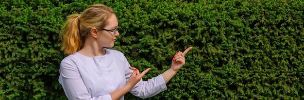 Femme médecin avec les doigts pointent vers le haut. nutritionniste en blouse blanche et verres avec espace copie.