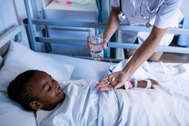 Femme médecin donnant des médicaments au patient