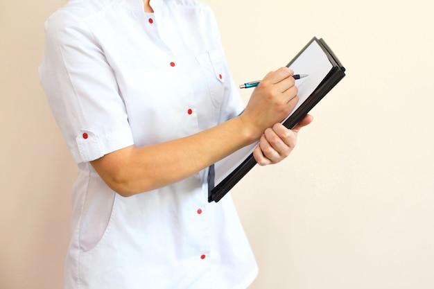 Femme médecin avec un dossier noir en uniforme debout et écrit des recommandations au patient.