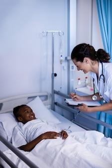 Femme médecin écrit sur le presse-papiers tout en interagissant avec le patient
