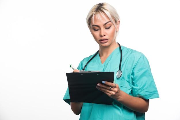 Femme médecin écrit quelque chose sur le presse-papiers avec un stylo sur une surface blanche