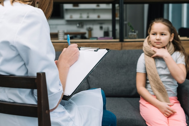 Femme médecin, écriture, presse-papiers, stylo, devant, fille, s'asseoir sofa