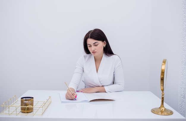 Une femme médecin est assise à une table et prend une note