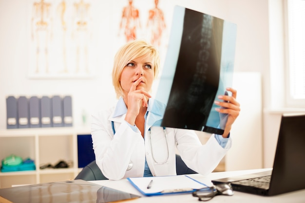 Femme médecin étudie la radiographie de la colonne vertébrale