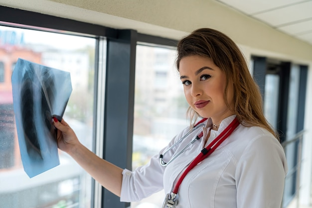 Femme médecin examinant un film radiographique thoracique, ayant des questions sur le diagnostic du patient à l'hôpital.