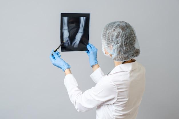 Femme médecin examinant l'image aux rayons x des jambes du nouveau-né. isolé