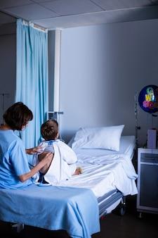 Femme médecin examinant le patient avec stéthoscope