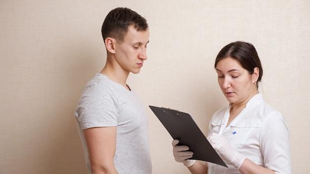 Une femme médecin examine la tête d'un homme chauve et remplit une carte d'histoire.