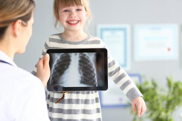 Femme médecin, examiner, petite fille, à, ultra, moderne, balayage, tablette, pc, dispositif
