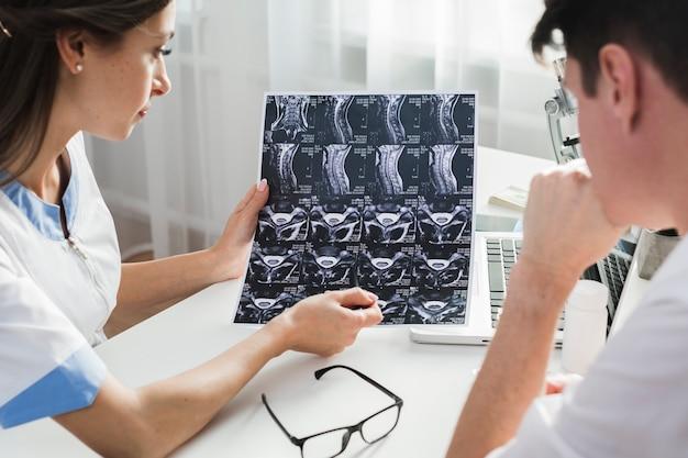 Femme médecin expliquant une radiographie au patient