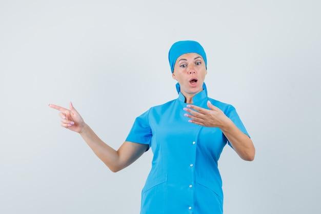 Femme médecin faisant semblant de tenir un téléphone portable, pointant de côté en uniforme bleu et à la surprise. vue de face.