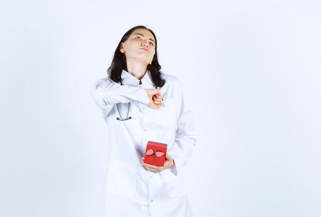 Femme médecin faisant signe de la main tout en levant et tenant son cadeau en face du mur rouge
