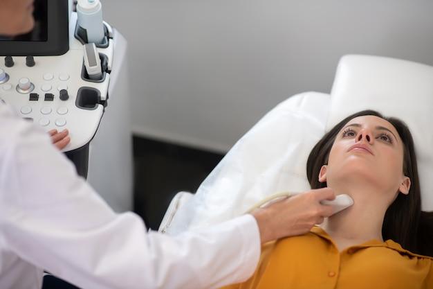 Femme médecin faisant un test de la glande thyroïde par ultrasons à une patiente