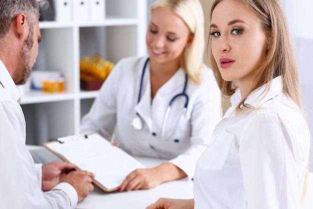 Femme médecin de famille écoute attentivement jeune couple