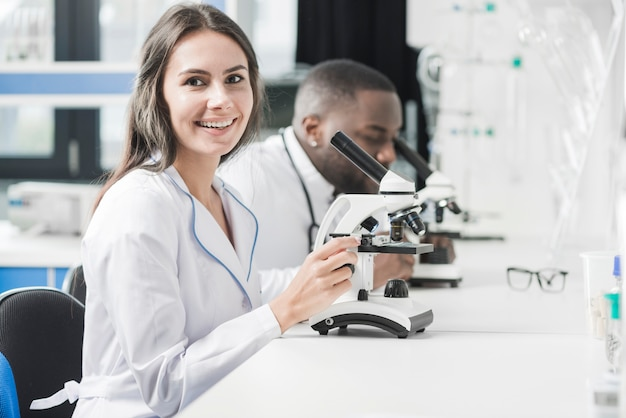 Femme médecin gai au micoscope