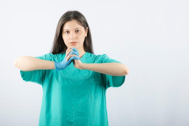 Femme médecin en gants médicaux montrant les mains sur blanc.