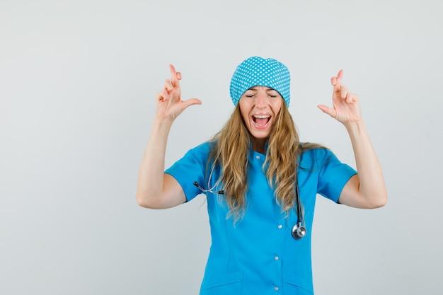 Femme médecin gardant les doigts croisés en uniforme bleu et l'air heureux.