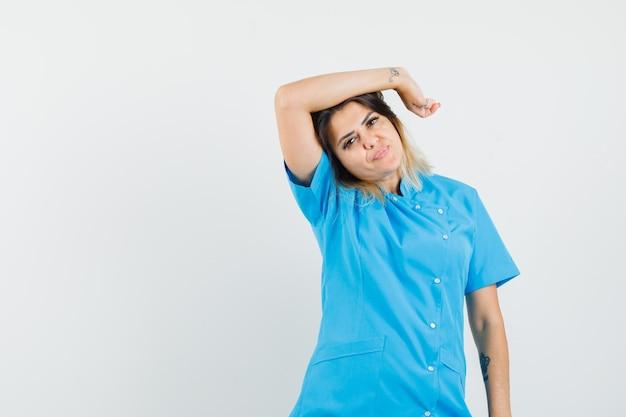 Femme médecin gardant la main levée au-dessus de la tête en uniforme bleu et à la jolie